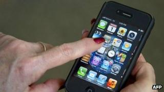A woman uses her Apple iPhone in this 1 March 2012 file photo
