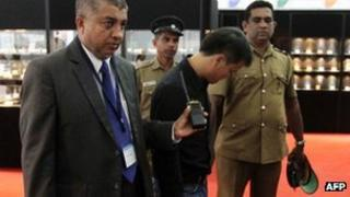 A Sri Lankan security official (L) and uniformed police escort a Chinese national (C) who was accused of stealing a $13,800 diamond by swallowing it