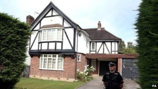 A police officer outside the home of Saad al-Hilli in Claygate