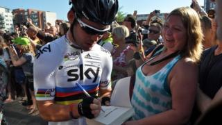 Mark Cavendish signs a book for a fan in Ipswich