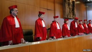 Andreas Vosskuhle (5th L), president of the second senate of the German Constitutional Court, and judges arrive to announce the verdict on the commuter tax allowance in Karlsruhe, in this December 9, 2008 file photo.