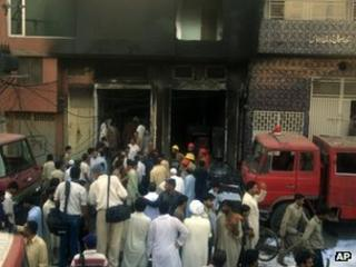 People gather outside the Lahore factory