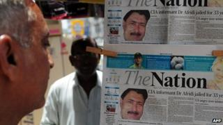 A Pakistani man reads a newspaper bearing the photograph of Shakil Afridi (May 2012)