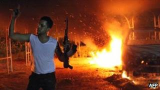 Armed man stands infront of burning car