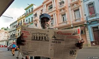 Man reading newspaper in Havana