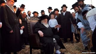 Hasidic rabbi in a wheat field attended by his followers