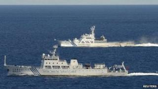 Chinese marine surveillance ship cruising with Japan Coast Guard ship in the background near the disputed islands on 14 September 2012