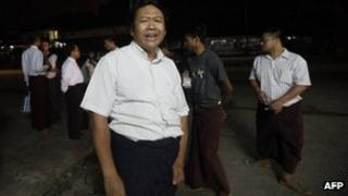 """Political prisoner and NLD member Nay Win addresses reporters after he reached the National League for Democracy (NLD) headquarters (background) following his release from detention in Myanmar""""s biggest city Yangon on September 17, 2012."""