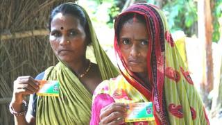 Two women in Samastipur district showing off their health insurance smart cards.