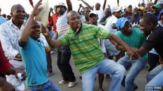 Striking miners dance and cheer after they were informed of a wage increase offer by Lonmin on 18 September 2012