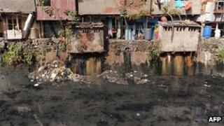 Dwellings overlooking sewer in Dharavi