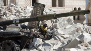 A Syrian boy plays on a destroyed tank near a destroyed mosque in Azaz, northern Syria. Photo: 23 September 2012