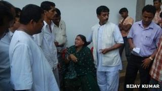 Woman being comforted after the stampede in Deoghar