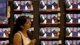 An Indian girl watches Prime Minister Manmohan Singh address the nation on the current economic situation of the country, at an electronics showroom in Mumbai, India, Friday, Sept. 21, 2012.