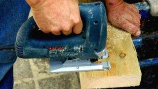 Carpenter sawing through wood