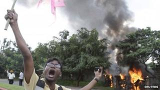 A pro-Telangana supporter shouts slogans near police vehicles which were set on fire by the supporters during a protest in the southern Indian city of Hyderabad September 30, 2012.
