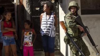 Residents watch soldiers patrolling the Fogo Cruzado slum in Rio de Janeiro ahead of Sunday's municipal elections