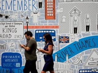 Man and woman walk past mural using smartphones