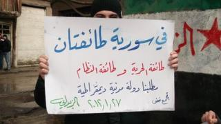 """Syrian activist holding sign reading """"There are two sects in Syria - the sect of freedom and the sect of the regime"""""""