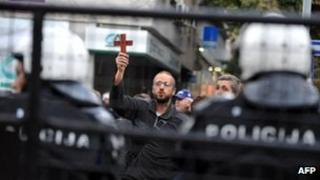 A Christian protester waves a cross outside a Belgrade gallery showing the gay-themed exhibition Ecce Homo, 3 October