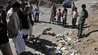 Local men inspect the site of the shooting in Sanaa