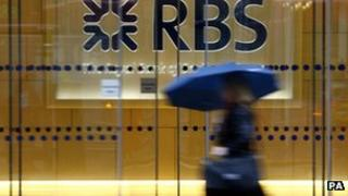 A woman walks past an RBS branch