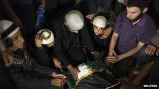 "The son of Salafi Islamist Hisham al-Saedni sits next to his father""s body during his funeral at a mosque"