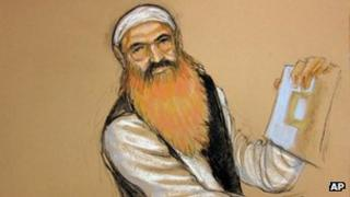 Khalid Sheikh Mohammed holds up a piece of paper during a court recess at Guantanamo Bay US Naval Base in Cuba 15 October 2012