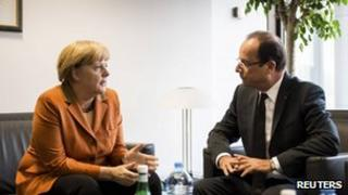 German Chancellor Angela Merkel talks with French President Francois Hollande ahead of an EU summit in Brussels