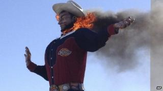 Fire begins to engulf the Big Tex displayed at the State Fair of Texas in Dallas 19 October 2012