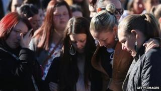People comfort each other as they gather for a local community vigil outside Ely Fire Station