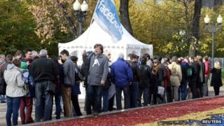People queue by a polling station in Moscow to take part in a vote to elect a Coordinating Council of the Russian opposition movement