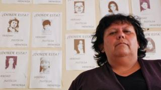 Lorena Pizarro in front of photos of the disappeared in Chile