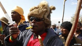 Striking miners chant slogans as they gather at the AngloGold Ashanti mine in Carletonville, north-west of Johannesburg, 25 October