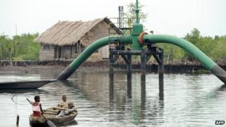 Children in a boat pass an oil pipeline head near their home in Rivers state April 2011