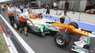 Pit crew push the car of Force India Formula 1 driver Paul di Resta of Britain in the pit lane at the Buddh International Circuit