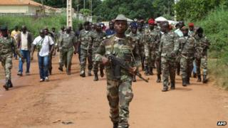 Guinea Bissau soldiers walk on October 21, 2012 in a street of Bissau after gunmen raided a Guinea-Bissau army barracks in the capital