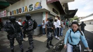 Policemen stand guard after stores were looted during protests against the law on 26 October.