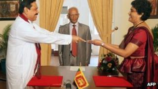 """This handout photo taken on May 18, 2011 and released by Sri Lanka""""s Presidential Secretariat shows President Mahinda Rajapakse (L) presenting a letter of appointment to Shirani Bandaranayake who became Sri Lanka""""s first woman chief justice."""