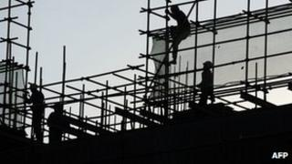 Workers erecting roof on building