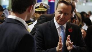 David Cameron gestures while speaking at a fair in Dubai