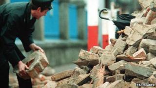 Man in uniform digs through rubble
