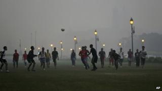 Boys play soccer at a park enveloped by a blanket of smog, caused by a mixture of pollution and fog, in New Delhi, India, Tuesday, Nov. 6, 2012.