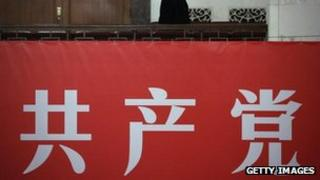 """Two members of security staff usher pass the banner displaying the words """"Communist Party"""" during a meeting of the 18th Communist Party Congress at the Great Hall of the People in Beijing, 09 Nov 2012"""