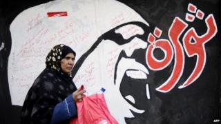 A woman walks past graffiti which reads 'revolution'