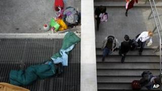 A homeless person sleeps on a metro ventilation grill as commuters enter Syntagma station in Athens