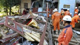 Volunteers clear debris from a pagoda damaged by Sunday's earthquake in Mandalay