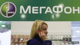 A customer speaks on her phone inside a Megafon shop in St Petersburg