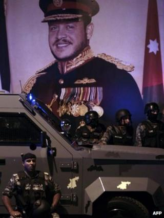 Riot police stand in front of a picture of King Abdullah II in Amman (13 November 2012)