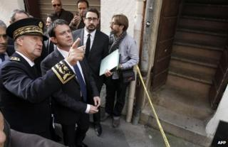 French Interior Minister Manuel Valls listens to South Corsica's Prefect, Patrick Strzoda , at the scene of Jacques Nacer's murder in Ajaccio, 15 November